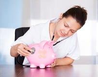 Doutor com banco piggy e estetoscópio Fotografia de Stock