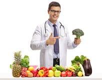 Doutor com brócolis que aponta atrás de uma tabela com fruto e vege foto de stock