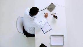 Doutor com cardiograma que chama o telefone na clínica video estoque