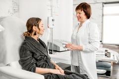 Doutor com cliente da mulher em um recurso médico foto de stock royalty free