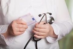 Doutor com estetoscópio e dinheiro em um fundo borrado Imagens de Stock Royalty Free