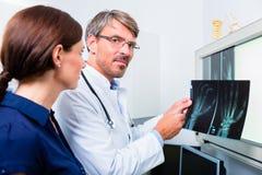 Doutor com imagem do raio X da mão paciente Foto de Stock