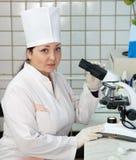 Doutor com o microscópio no laboratório Fotografia de Stock