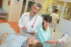 Doutor com o paciente de questão da prancheta imagem de stock royalty free