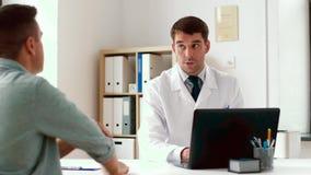 Doutor com o paciente do portátil e do homem no hospital vídeos de arquivo