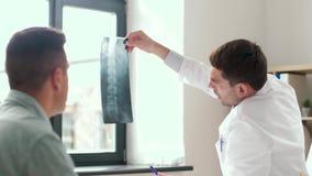 Doutor com o paciente do raio X e do homem no hospital video estoque