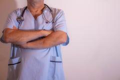 Doutor com os braços cruzados Torso do homem em vestuários médicos fotografia de stock