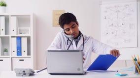 Doutor com papéis que chama o telefone no hospital video estoque