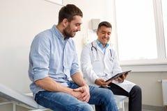 Doutor com PC da tabuleta e paciente do homem no hospital imagens de stock