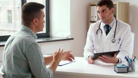 Doutor com PC da tabuleta e paciente do homem no hospital filme