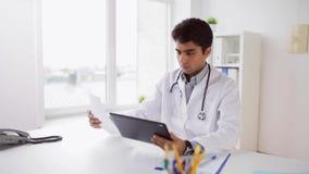 Doutor com PC e papéis da tabuleta no hospital vídeos de arquivo