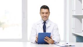 Doutor com PC e prancheta da tabuleta no hospital vídeos de arquivo
