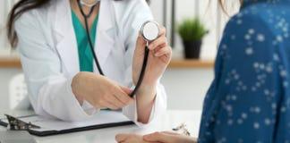 Doutor com um estetoscópio na mão O médico está pronto para examinar seu paciente fêmea foto de stock