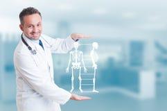 Doutor considerável do ortopedista que guarda o holograma modelo de esqueleto em h fotografia de stock royalty free