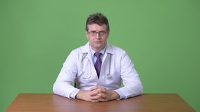 Doutor considerável maduro do homem contra o fundo verde filme