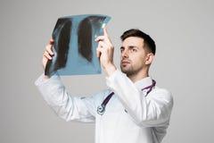 Doutor considerável novo que olha o raio X no fundo branco imagem de stock
