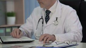 Doutor da ciência médica que escreve o artigo científico para o compartimento, usando o portátil vídeos de arquivo