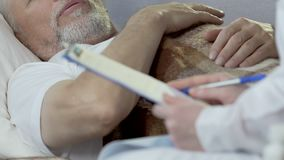 doutor da Em-chamada que senta-se ao lado do homem idoso que encontra-se na cama, escrevendo para baixo sintomas video estoque