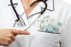 Doutor da mulher com dinheiro da moeda do polimento da exibição do estetoscópio no bolso do avental, na corrupção ou no conceito  Imagens de Stock Royalty Free