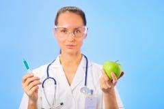 Doutor da mulher nova que injeta a maçã verde Imagem de Stock