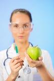 Doutor da mulher nova que injeta a maçã verde Fotos de Stock Royalty Free