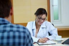 Doutor da mulher que fala a seu paciente masculino no escritório fotografia de stock