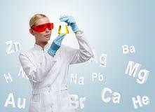 Doutor da mulher que faz a combinação química na garrafa de Erlenmeyer foto de stock
