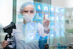 Doutor da mulher que pressiona botões com vários ícones médicos Foto de Stock Royalty Free