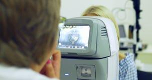 Doutor da mulher que trabalha com a máquina do refractometer Close-up da tecnologia da oftalmologia video estoque