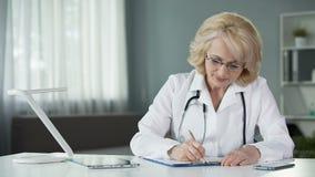 Doutor da senhora que enche-se no formulário do seguro de saúde antes de continuar tratar o paciente vídeos de arquivo