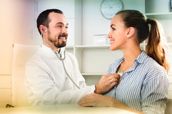 Doutor de consulta do homem do visitante fêmea no hospital imagens de stock royalty free