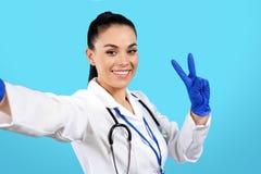 Doutor de encantamento da jovem mulher com gesto da paz da mostra do estetoscópio sobre o fundo azul foto de stock