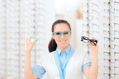 Doutor de olho Comparing Contacts aos monóculos para a correção da visão imagem de stock