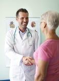 Doutor de sorriso com paciente Fotografia de Stock Royalty Free