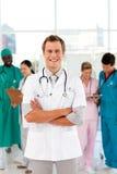 Doutor de sorriso com sua equipe no fundo Fotografia de Stock Royalty Free
