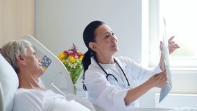 Doutor de sorriso da mulher que discute a varredura do raio de x com seu paciente envelhecido filme
