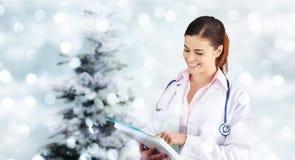 Doutor de sorriso do Natal com o dobrador em luzes borradas com árvore imagem de stock royalty free