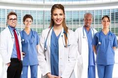 Doutor de sorriso na frente de sua equipa médica fotografia de stock