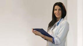 Doutor de sorriso novo com o estetoscópio e a prancheta que estão na sala branca do hospital filme