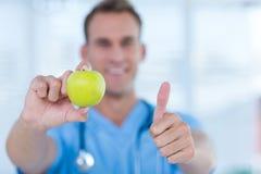 Doutor de sorriso que apresenta uma maçã verde Fotografia de Stock