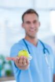 Doutor de sorriso que apresenta uma maçã verde Imagem de Stock Royalty Free