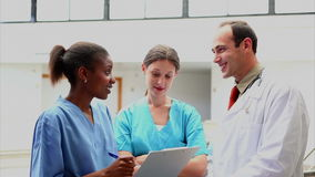 Doutor de sorriso que escuta uma enfermeira que guarda uma prancheta vídeos de arquivo