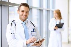 Doutor de sorriso que espera sua equipe ao estar ereto fotos de stock royalty free