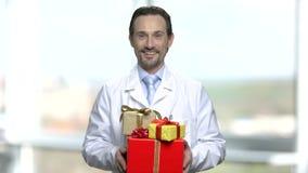 Doutor de sorriso que guarda o grupo de caixas de presente vídeos de arquivo