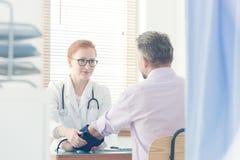 Doutor de sorriso que mede a pressão paciente do ` s foto de stock