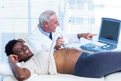 Doutor de sorriso que mostra movimentos do bebê na tela Fotografia de Stock Royalty Free