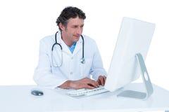 Doutor de sorriso que trabalha em seu portátil Foto de Stock