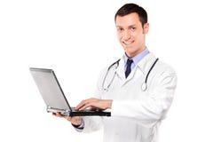 Doutor de sorriso que trabalha em um portátil Imagens de Stock Royalty Free