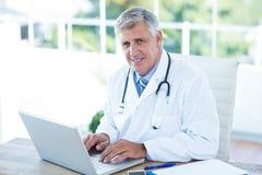 Doutor de sorriso que trabalha no portátil em sua mesa Imagens de Stock Royalty Free