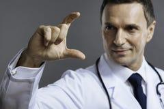 Doutor deleitado que mostra o gesto com sua mão fotografia de stock